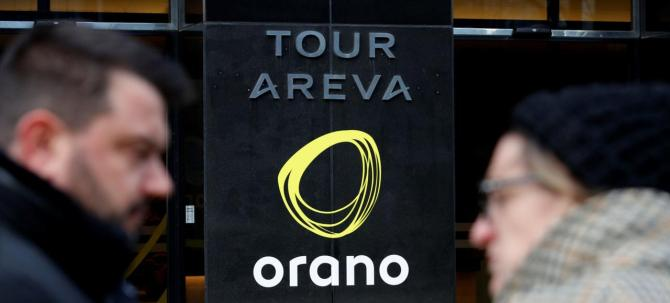 "People walk past the new company name ""Orano"" of the French nuclear fuel group Areva installed on the Areva Tower in La Defense near Paris"