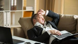 Businessman in suit lying on a couch with two cellphones and laptops, sleeping. Exhausted man relaxing in office early morning. Responsible executive working fell asleep.