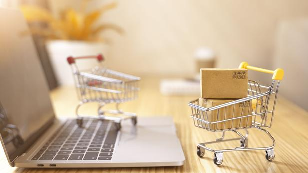 Online shopping and delivery service concept.Brown paper boxs in a shopping cart with laptop keyboard on wood table in office background.Easy shopping with finger tips for consumers.